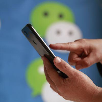 Kännykkää pitelevä käsi. Taustalla WeChat-sovelluksen logoja.