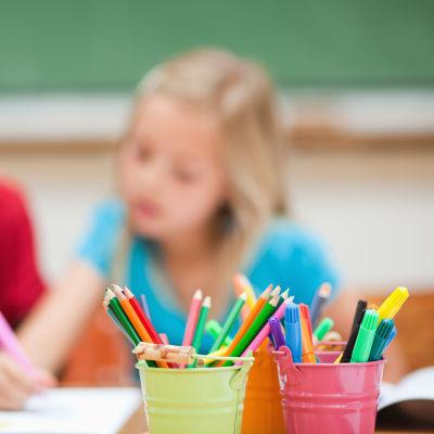 I förgrunden pennor i burkar. I bakgrunden två elever som ritar.