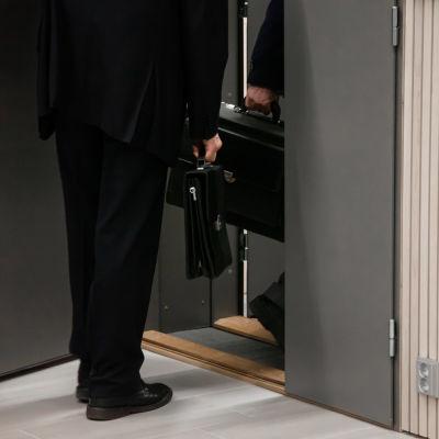 Anonyymit miehet menevät salkut käsissä Etelä-Karjalan käräjäoikeuden sali numero 2:een Lappeenrannassa.