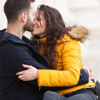 Leende kvinna i gul jacka lutar sig mot mörkklädd man med skägg