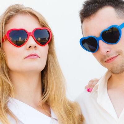 Blond kvinna och mörkhårig man, båda  i hjärtformade solglasögon