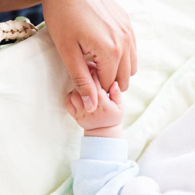Kvinnohand håller i en babyhand vid en babysäng.