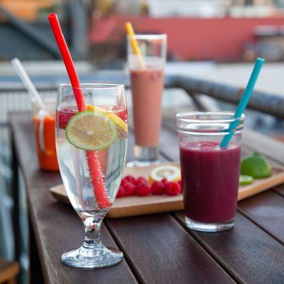 Glas med sugrör i står på ett bord. Glasen har olika saker i, t.ex. smoothie och vatten. På bordet finns också en bricka med frukt.