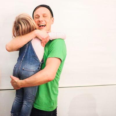 En man håller i ett barn.