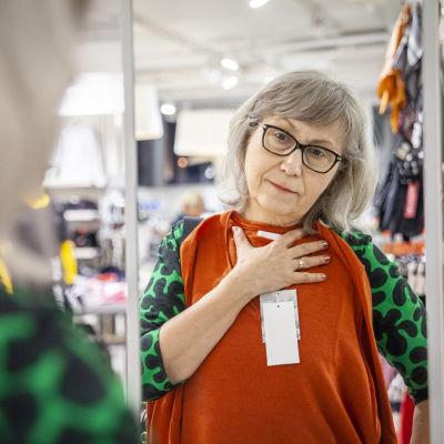 Kuopiolainen Jaana Iso-Ahola sovittelee paitaa peilin edessä Moda -liikkeessä.