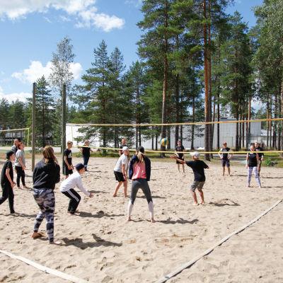 Ungdomar spelar beachvolleyboll på en sandig plan vid en idrottsanläggning.