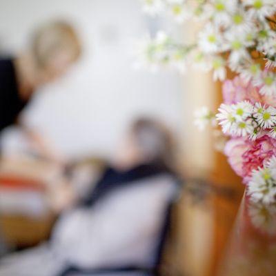 I förgrunden syns en bukett med blommor som står på ett bord. I bakgrunden syns en åldring som får hjälp av en yngre person, anställd, på ett äldreboende.