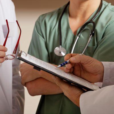 Läkare som tittar på en patientjournal. Inga ansikten syns, bara händer och läkarrockar.
