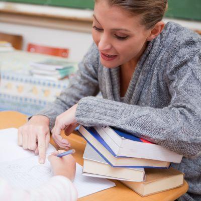 En lärare hjälper en elev i skolan.