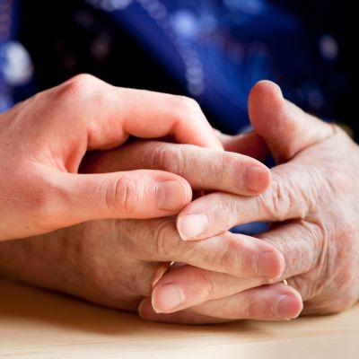 närbild på en äldre och en yngre persons händer