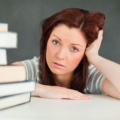 flicka i tonåren ser trött ut, vilar sig mot pulpeten, framför henne finns en hög med böcker