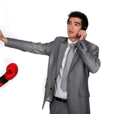en kvinnlig kollega med boxningshandskar står mot en manlig kollega som ignorerar kvinnan, talar istället i telefonen.