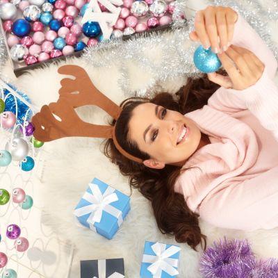 Leende kvinna ligger på golvet omgiven av julprydnader