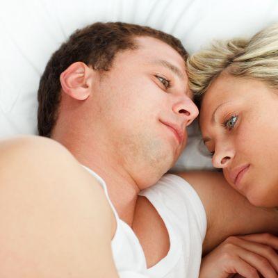 Man och kvinna ligger vända mot varandra i en säng, ser fundersamma ut