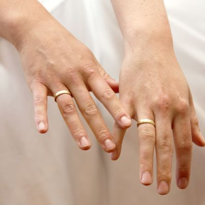 Händer med vigselringar.