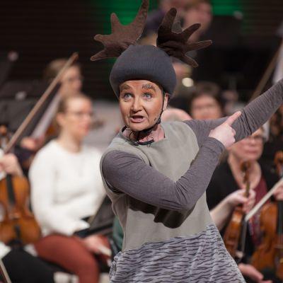 Sari Kallioranta Piilometsän soitinsadun hahmona, takana näkyy orkesteri