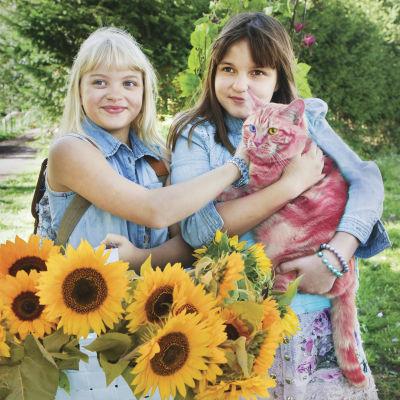 Onneli och Anneli (Lilja Lehto och Aava Merikanto) står invid ett fång med solrosor och håller en röd katt i famnen.