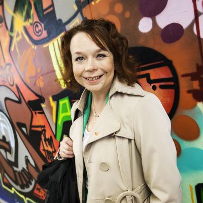 Kulttuuri- ja asuntoministeri Pia Viitanen graffitiseinän edessä