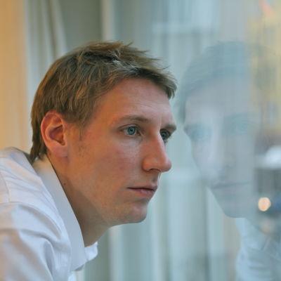 Pekka Strang i profil tittar ut genom ett fönster.