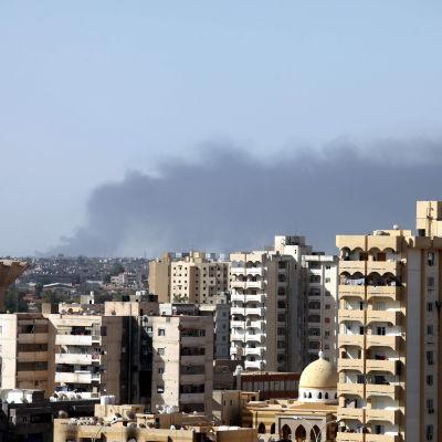 Rök stiger från strider kring flygplatsen i Tripoli.