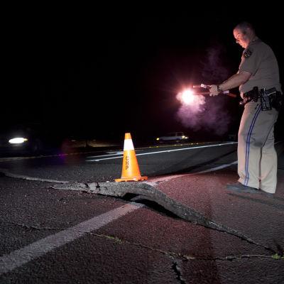 En polisman omdirigerar trafiken vid en väg som skadats vid jordskalvet.