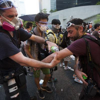 Folk tvättar av sig tårgas och pepparspray vid demonstrationerna i Hong Kong.