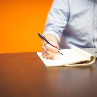Man med dator skriver på ett anteckningsblock.