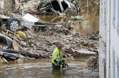 En man står i ett översvämmat område med vatten upp till höfterna.