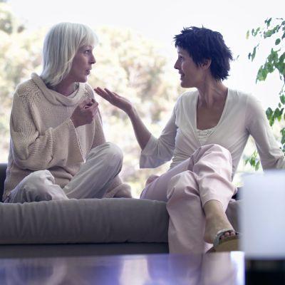 Två kvinnor sitter vända mot varandra och pratar och gestkulerar