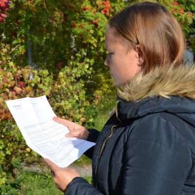 Lotta Björklöf fotograferad från sidan då hon står och tittar på brevet som kom från Caruna.