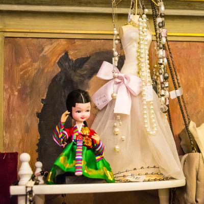 Diverse prylar på basaren, docka och dockkläder