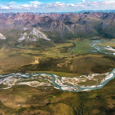 Alaskan arktisen luonnonsuojelualueen maisemaa kirkkaan sininen joki ja taustalla vuorenhuippuja
