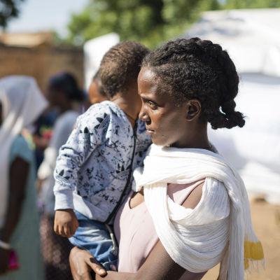 En kvinna med ett barn i famnen.