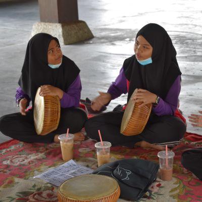 Tre kvinnor i burka sitter på en matta på golvet och spelar handtrumma.