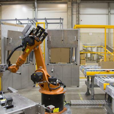 En orange robot som monterar ihop paket i postens logistikcentral för näthandel i Vanda.
