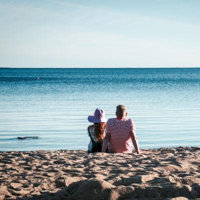 Kvinna med hatt och man i randig t-skjorta sitter på en sandstrand och tittar ut mot havet.