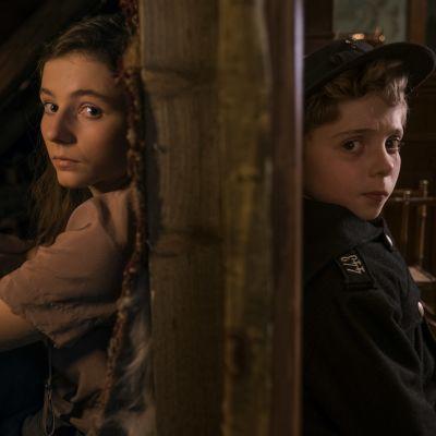 Jojo och Elsa sitter lutade mot varsin sida av en vägg.