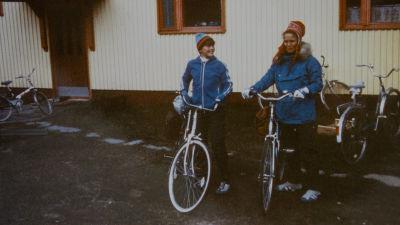 Kuvassa on Priitta Pöyhtäri-Tröen 13-vuotiaana äitinsä kanssa. Molemmilla on siniset takit ja pyörät.