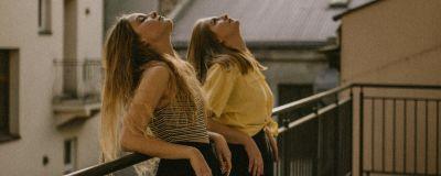 Två tjejer lutar mot ett räcke och tittar uppåt.