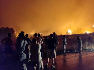 Flera människor står och tittar på en skogsbrand i Limni i Grekland.