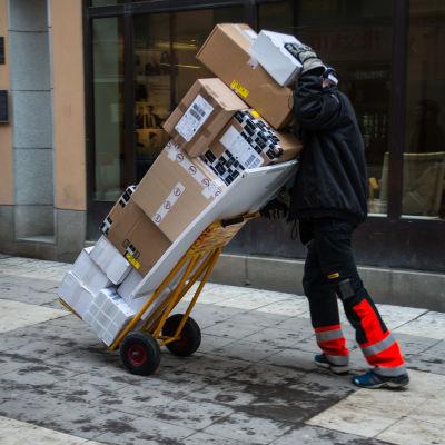 En person skuffar en bagagekärra med ett tiotal större paket på en snöig trottoar.