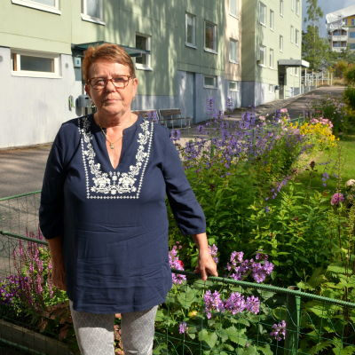 En kvinna står framför en blomrabatt framför ett högus.