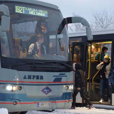 Två bussar som står stilla vid en busstation. Ungdomar stiger ut ur ena bussen