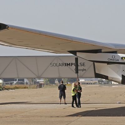 Mekaanikot tutkivat lentokentällä seisovaa lentokonetta.