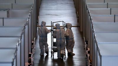 Tre sjukvårdare i full skyddsutrustning går längs en korridor i ett tillfälligt coronasjukhus.