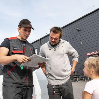 Tuomas kosonen ja tytär kuuntelemassa katsastuksen loppuraporttia. Katsastusmies Joonas Aaltonen antaa yhden huomautuksen, mutta muuten auto on kunnossa.