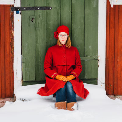 Maria Turtschaninoff sitter vid en grön dörr.