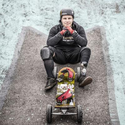 Matti Suur-Hamari istuu asvaltilla.