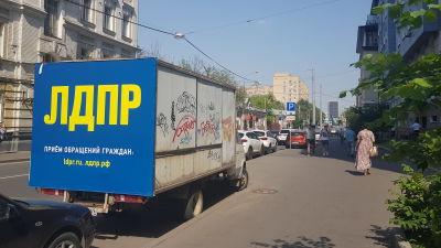 """En lasbil i stadsmiljö. På lastbilen står det på ryska """"LDPR, ta kontakt per mejl""""."""