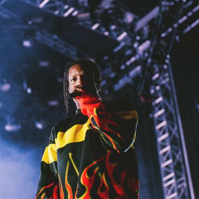 Liekkipaitaan pukeutunut Asap Rocky katsoo suoraan kameraan Blockfest-lavalta. Kuva on otettu yläviistoon ja rajattu artistin vyötäröstä alaspäin.